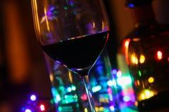 Закройте вверх красного бокала с бутылками алкоголя и красочного электрического света стоковое фото rf