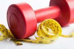 Закройте вверх красного веса гантели с измеряя лентой Стоковая Фотография