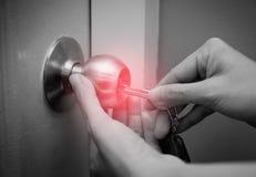 Закройте вверх красного пятна руки женщины используя ключ для открывать или запирать белую дверь стоковые изображения rf
