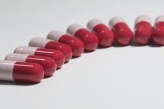 Закройте вверх красной и розовой капсулы probiotics Стоковое Изображение