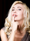 Закройте вверх красных губ обольстительного белокурого пальца повышения девушки к ее рту Позволенный ему наш секрет Стоковое фото RF