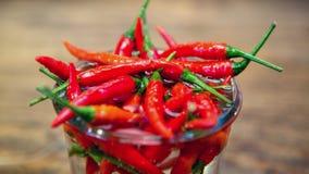 Закройте вверх красных chilis в опарнике с водой Стоковое Изображение