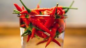 Закройте вверх красных chilis в опарнике с водой Стоковые Изображения