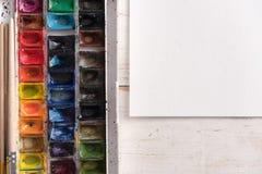 Закройте вверх красок акварели в ведре и белой бумаге Стоковое фото RF