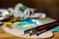 Закройте вверх красок и щеток масла на палитре Стоковые Изображения RF
