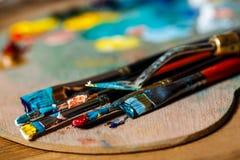 Закройте вверх красок и щеток масла на палитре Стоковые Фото