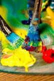 Закройте вверх красок и щеток масла на палитре Стоковая Фотография