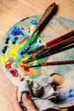 Закройте вверх красок и щеток масла на палитре Стоковое Фото
