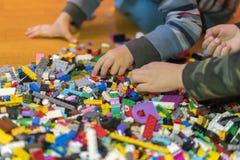 Закройте вверх красочных пластиковых кирпичей на поле раньше учащ Превращаясь игрушки Конструктор детей пластиковый на поле стоковое фото
