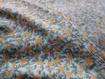 Закройте вверх крошечных цветков и листьев на ткани Стоковые Фотографии RF