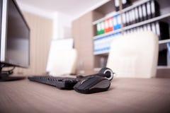 Закройте вверх клавиатуры, мыши и шлемофона на таблице офиса Стоковые Изображения