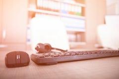Закройте вверх клавиатуры, мыши и шлемофона на таблице офиса Стоковое Изображение RF