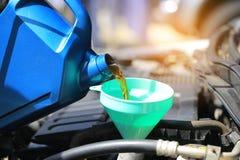 Закройте вверх лить свежее масло к двигателю автомобиля в обслуживании ремонта автомобилей, маслу изменения стоковые фотографии rf