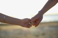 Закройте вверх 2 любовников соединяя руки Детализируйте силуэт человека и женщины держа руки над предпосылкой озера заход солнца  Стоковые Изображения RF