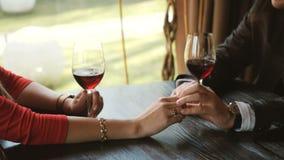 Закройте вверх любя пар держа руки и clinking стекла красного вина во время романтичного обедающего акции видеоматериалы