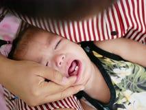 Закройте вверх маленького азиатского ребёнка, одного годовалого, плача как ее новые зубы нажимая вне стоковая фотография rf