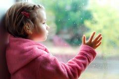 Закройте вверх маленькой милой девушки в розовых взглядах купального халата уныло из окна Сидеть на силле окна стоковые изображения rf