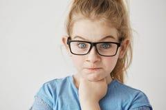 Закройте вверх маленькой милой девушки при большие голубые глазы и светлые волосы смотря камеру с сердитым выражением стороны и п Стоковое фото RF