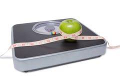 Закройте вверх масштаба, ленты и яблока изолированных на белизне Стоковые Изображения RF