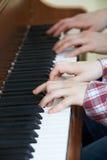 Закройте вверх мальчика играя дуэт рояля с учителем стоковое изображение rf