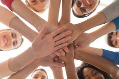 Закройте вверх международных женщин штабелируя руки стоковые изображения rf