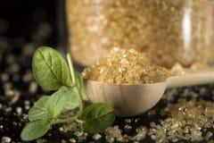 Закройте вверх меньшей ложки woode заполненной с желтым сахарным песком на шифере Стоковые Изображения RF