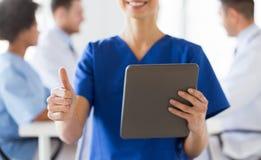 Закройте вверх медсестры при ПК таблетки показывая большие пальцы руки Стоковые Фото