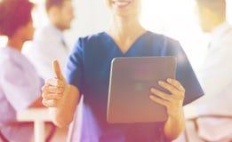 Закройте вверх медсестры при ПК таблетки показывая большие пальцы руки Стоковое Фото