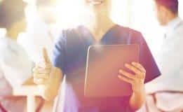 Закройте вверх медсестры при ПК таблетки показывая большие пальцы руки Стоковая Фотография RF