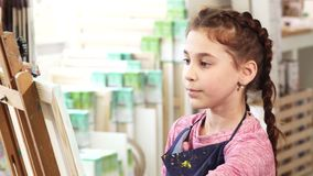 Закройте вверх милой картины маленькой девочки на мольберте на школе видеоматериал