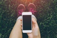 Закройте вверх молодого азиатского здорового телефона обнесенное решеткой места в суде рук ` s женщин Стоковые Фотографии RF