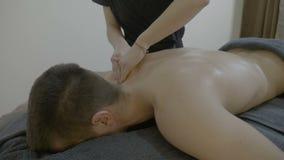 Закройте вверх молодого женского masseuse делая detensioning и расслабляющий массаж к привлекательному мужскому пациенту в центре акции видеоматериалы