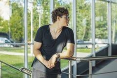 Закройте вверх молодого человека стоя рядом с поручнями и окнами на станции метро стоковое фото rf