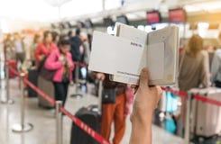 Закройте вверх молодой женщины держа пасспорт и прикройте посадочный талон на приемной счетчиков авиапорта с много людей в предпо Стоковое Изображение