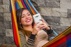 Закройте вверх молодой красивой женщины в гамаке используя ее мобильный телефон, в запачканной предпосылке Стоковые Фото
