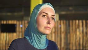 Закройте вверх молодой sporty мусульманской женщины в hijab делая спорт на имитаторе видеоматериал