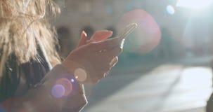 Закройте вверх молодых женских рук используя телефон, outdoors акции видеоматериалы