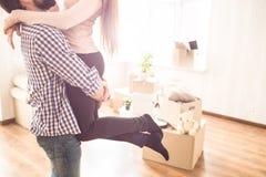 Закройте вверх молодых пар в светлой комнате Молодой человек держит его жену на руках Коробки с различной Стоковые Изображения RF