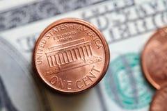 Закройте вверх монеток цента США на предпосылке долларовой банкноты Стоковые Изображения