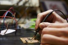 Закройте вверх монтажной платы инженер-электрика паяя Стоковое Изображение