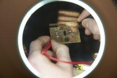 Закройте вверх монтажной платы инженер-электрика паяя Стоковая Фотография