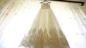 Закройте вверх модного платья свадьбы на вешалке, белых ботинках на поле и букете с розовыми розами в сток-видео