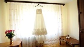 Закройте вверх модного платья свадьбы на вешалке, белых ботинках на поле и букете с розовыми розами в комнате сток-видео