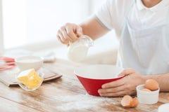 Закройте вверх молока мужской руки лить в шаре стоковые фото