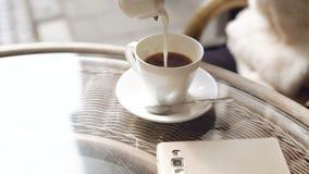 Закройте вверх молока потока девушки лить в чашку эспрессо 4K сток-видео
