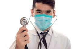 Закройте вверх молодого мужского доктора в форме и маске с представлять stathoscope изолированных на белой предпосылке Стоковые Изображения RF