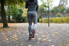 Закройте вверх молодой женщины бежать в парке осени Стоковые Изображения