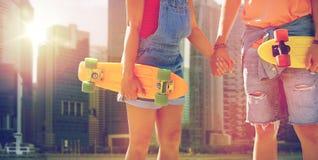 Закройте вверх молодых пар с скейтбордами в городе Стоковое фото RF