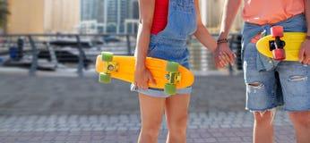 Закройте вверх молодых пар с скейтбордами в городе Стоковые Изображения RF
