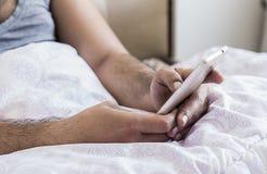 Закройте вверх молодых пальцев рук мужчины работая в кровати на sms мобильного телефона печатая на клавиатуре Стоковая Фотография